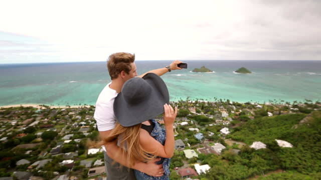 Happy couple taking selfie self-portrait photo hiking, Oahu, Hawaii video