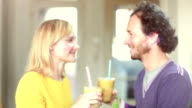 Happy couple toasting and drinking fruit smoothie video
