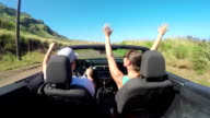 CLOSE UP: Happy couple with hands raised driving convertible along coastal road video