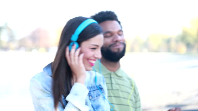 Happy couple with headphones listening to music and dancing video