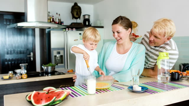 Happy couple with kid at the kitchen in the morning. Pregnant wife. Breakfast. video