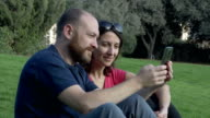 Happy couple with smartphone in the park video