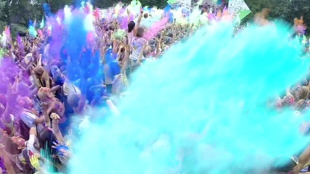 Happy crowd throws paint powder in air, festival atmosphere video