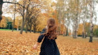 happy cute little girl with curly hair, in dress with polka dots runing through the autumn alley in the park slow mo video