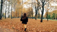 happy cute little girl with curly hair runing through the autumn alley in the park slow mo video