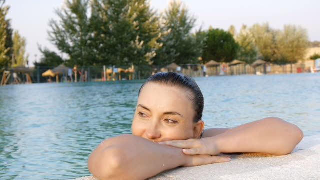Happy cute woman enjoys water on the edge of the pool video