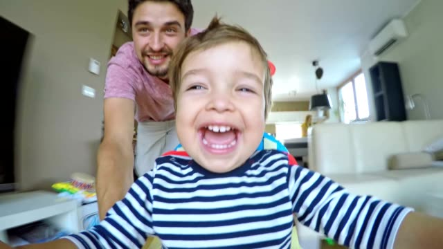 POV Happy dad pushing his son in the walker across the house video