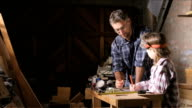 Happy dad teaches daughter about woodwork video