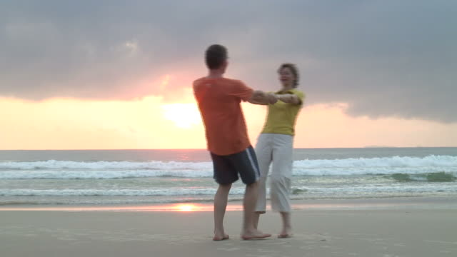 Happy dancing couple on a beach video