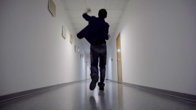 Happy dancing man walking down the long corridor video