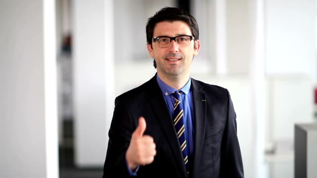 Happy designer giving thumbs up to camera video