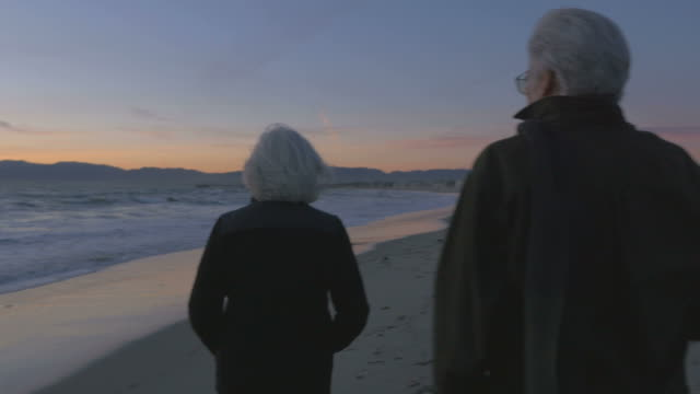 Happy elderly 60s couple walking and pointing along upscale beachfront at sunset video