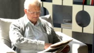 happy elderly man sits in a chair and reading a newspaper in a modern apartment video