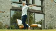 Happy elderly woman spinning in garden video