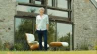 Happy elderly woman stretching in garden video