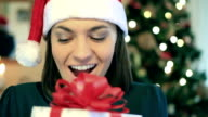 Happy excited woman gets present, christmas tree in background video