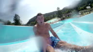 SELFIE: Happy excited young man sliding down the fast water slide in fun waterpark in sunny summer video