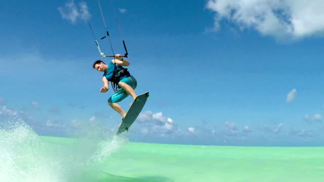 SLOW MOTION: Happy extreme kite boarder jumping and splashing water into camera video