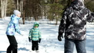 Happy family are playing in snowballs in winter park video