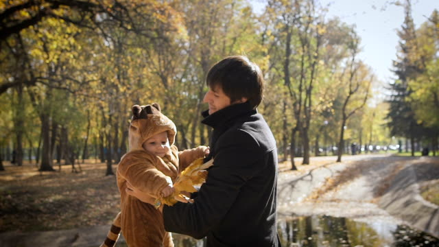 Happy family Dad throws child son up on a walk in the autumn leaf fall in park video
