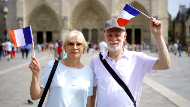 Happy family enjoying vacation. Seniors standing near Notre Dame of Paris. Waving French flags video