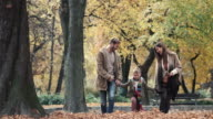 Happy family holding hands and having fun while walking in autumn. video