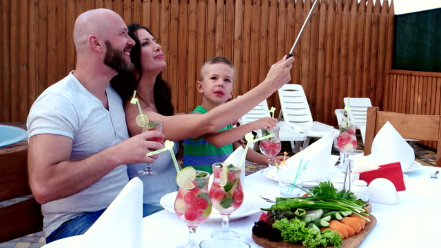 happy family, lunch, parents with children make the photos at mobile phone is placed on a stick selfi, cheerful gatherings video