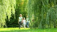 Happy family of four persons walks in park to camera video