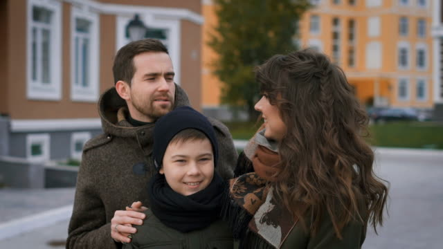 Happy family on a photo shoot. Mother, father and son. They pose for the camera. The family has an excellent mood. They want to capture forever in their memories and photos on this sunny video