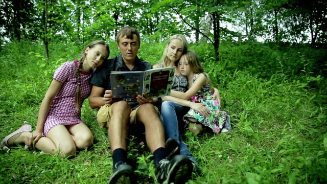 Happy family reading book in the park video