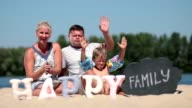 Happy family sitting on the beach and waving hello video