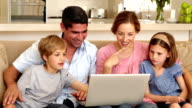 Happy family sitting on the sofa using laptop video