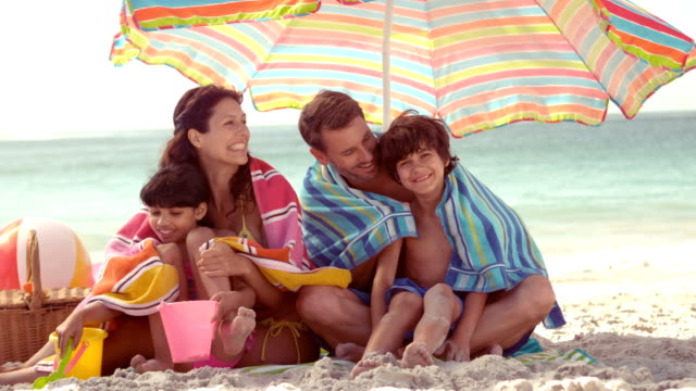 Happy family sitting under parasol video
