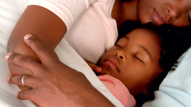 Happy family sleeping in bed video