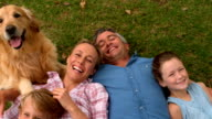 Happy family smiling at the camera with their dog video