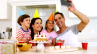 Happy family taking a selfie while celebrating a birthday video