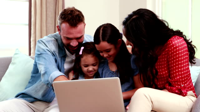 Happy family using laptop on sofa video