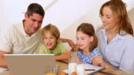 Happy family using laptop together at the breakfast table video