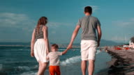 Happy family walking on the beach, in a summer day video
