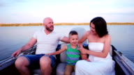 happy family walking on the waterfront, parents with a child on a summer outing, mom and dad are the hand of son, laughing merrily walking in nature, beautiful pier video