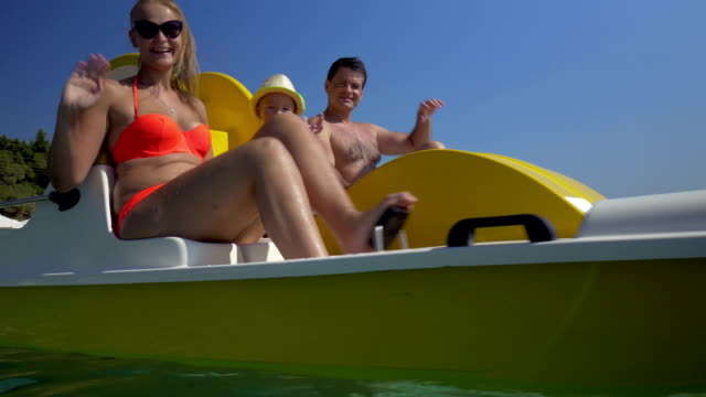 Happy family waving hands while sailing on pedal boat video