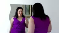 happy fat woman looking herself on the mirror and sanding a kiss video