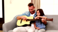 Happy father and daughter playing guitar video