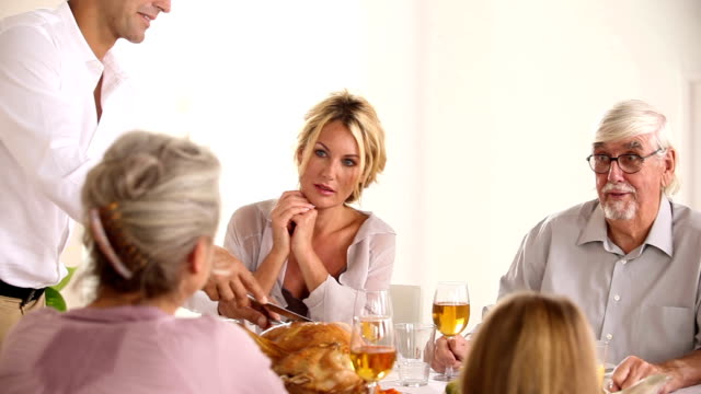 Happy father carving turkey at head of table video
