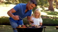 Happy father doing barbecue with her daughter video