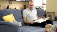 Happy father sitting on sofa invite his toddler daughter to read book together. video