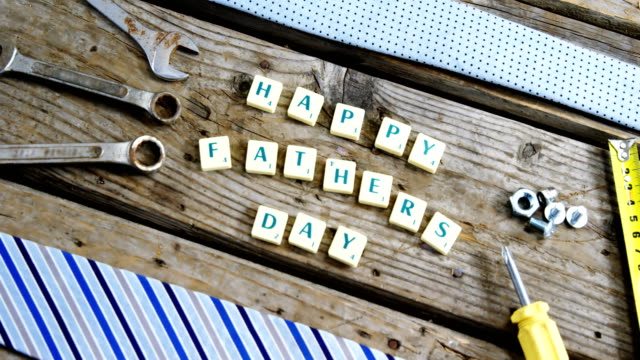 Happy fathers day block and old work tool arranged on wooden plank video