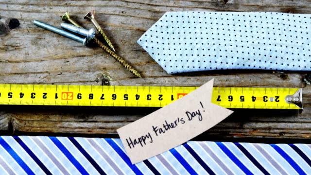 Happy fathers day card, tie, screw, measuring tape on wooden plank video