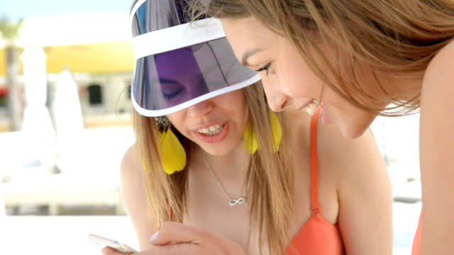 happy female friends in swimsuits using smartphone, watching photos or news video