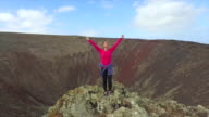 AERIAL: Happy female raising hands on top of volcanic crater video